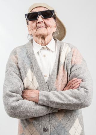 abuela: Retrato divertido de la abuela estudio que llevaba gafas y gorra de b�isbol, que se destaca por su derecho, aislado en blanco Foto de archivo