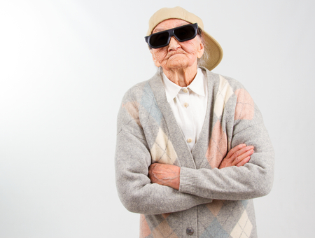 Funny grandmas studio portrait  wearing eyeglasses and baseball cap, who stands for her right,  isolated on white
