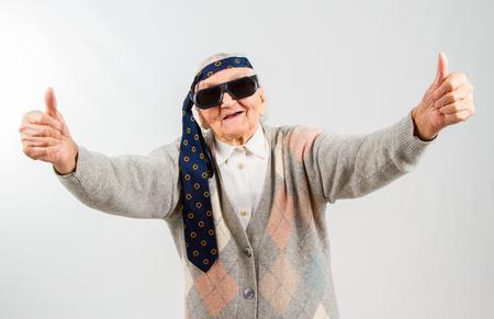 caras graciosas: Divertido del estudio de portarit con un empate en la frente de la abuela, que muestra los pulgares para arriba