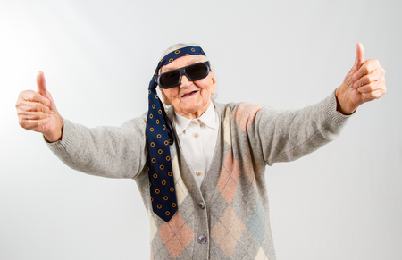 Funny grandma's studio portarit with a tie on her forehead, showing thumbs up Stockfoto