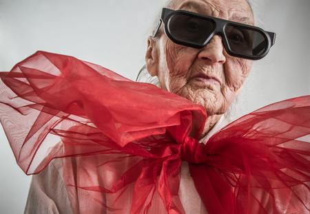 안경 세련된 할머니와 그녀의 목에 큰 붉은 나비