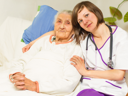 kind young female nurse caring for a very old femaile patient,in hospital photo