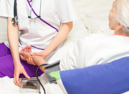 Young  nurse taking blood pressure  for  elderly patient lying in bed photo