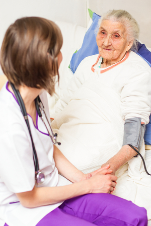 caring for: Happy joyful nurse caring for an elderly woman helping her days in nursing home.