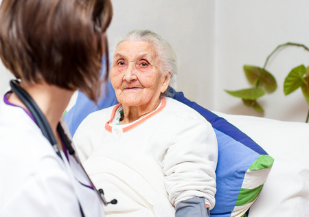 caring for: Young  nurse caring for  elderly patients helping their days in nursing home.