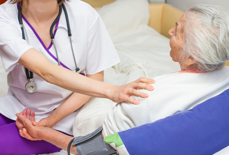 Young  nurse caring for an  elderly woman helping her days in nursing home.
