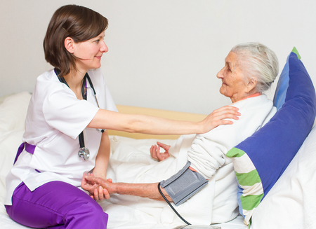 Happy joyful nurse caring for  an elderly woman  helping her days in nursing home. Standard-Bild