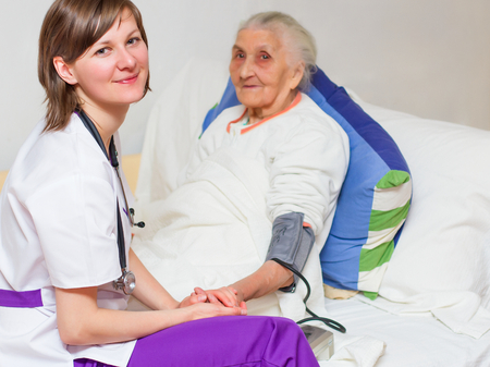 cancer patient: Happy joyful nurse caring for  an elderly woman  helping her days in nursing home. Stock Photo