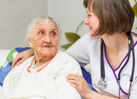 Happy joyful nurse caring for  an elderly woman  helping her days in nursing home. Archivio Fotografico