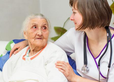 personne malade: Infirmi�re joyeux heureux s'occuper d'une femme �g�e aider ses jours en maison de soins infirmiers.