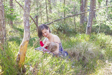 youn mother breastfeeding her baby in the forest in springtime photo