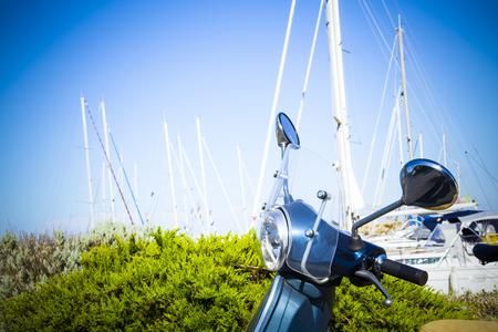 vespa piaggio: scooter d'epoca nel porto con longheroni in background