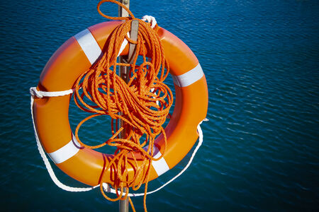 red life buoy hanging above the  water photo