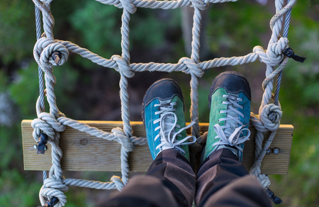 adventure sports: outdoor shoes on a rope grid , in an adventure park