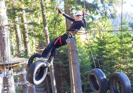 woung woman  hanging on tires in an adventure park in the forest photo