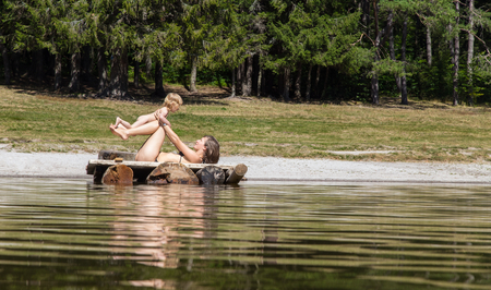 young mother playing with her toddler at the coastline of a lake in the forest photo