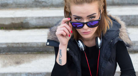 glancing: Beautiful woman glancing seductively above her sunglasses. Stock Photo