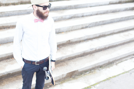 expressionless: Hipster guy holding a skateboard and standing.