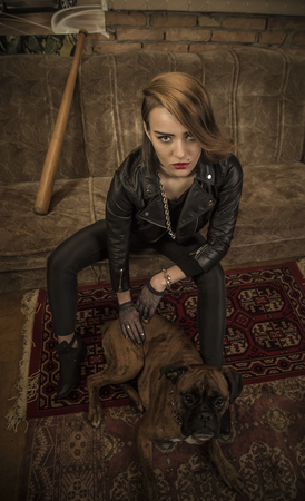 seductive couple: Beautiful woman with her bulldog pet sitting on a couch. Stock Photo