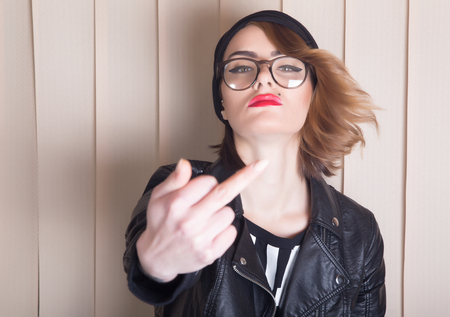Lady with leather jacket showing fuck-you sign.