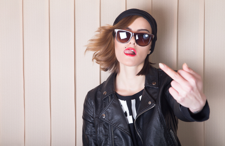 aggressive people: Beautiful lady in leather jacket showing middle finger.