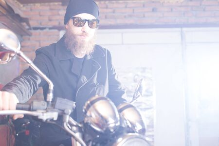 chopper: Hipster man with his chopper motorcycle posing.