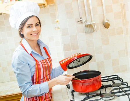 dinner wear: Beautiful woman cooking in the kitchen at home.