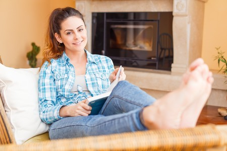 Beautiful woman at home relaxing while reading.