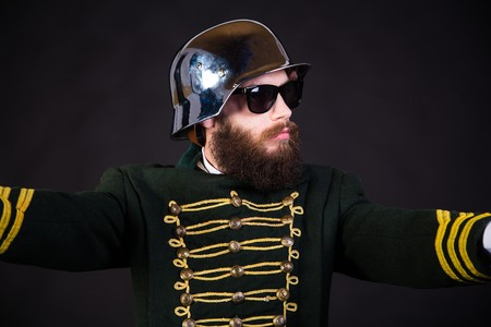 Man in cap and costume posing strangely. Stock Photo