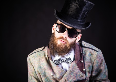 weird: Stylish hipster in weird outfit before a black background.