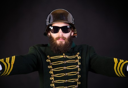 Hispter dressed as a military member but with sunglasses.