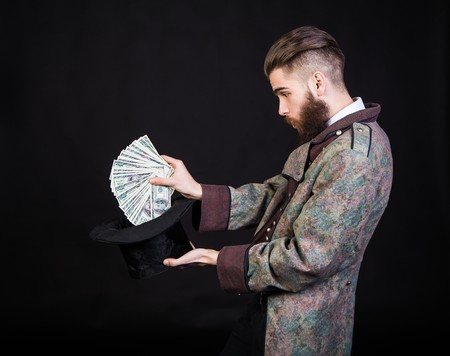 pulling money: Man pulling out money from a magical hat. Stock Photo