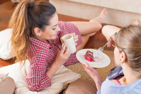 chitchat: Girlfriends talking near a cup of coffee and cake. Stock Photo
