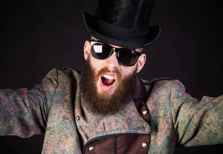 weirdo: Strangely elegant hipster man in an unusual outfit staring.
