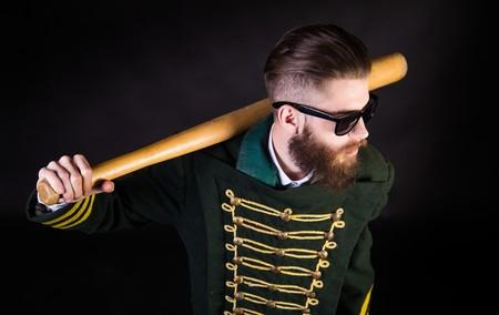 swag: Strange man in uniform and sunglasses holding a bat.