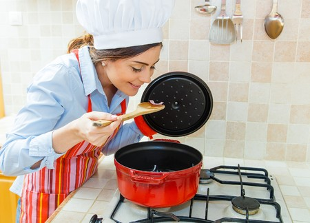wooden spoon: Woman chef smiling and cooking in red pot in the kitchen.