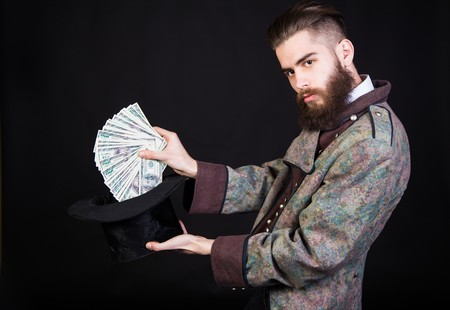 funny bearded man: Magician pulling out money from the magical hat.