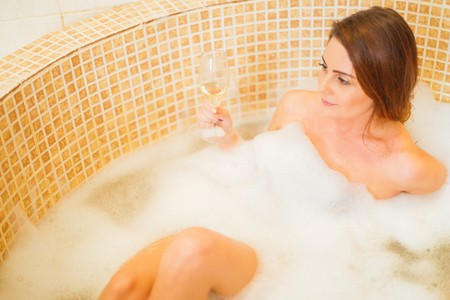 sensible: Beautiful lady in the foam bath drinking champagne.