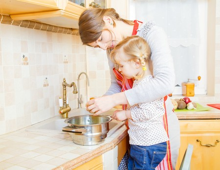 motherly: Little girl and mother cooking together in the kitchen.