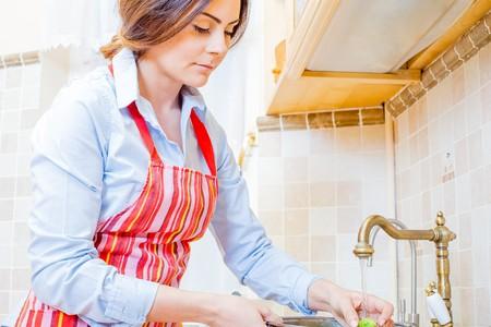 lavar trastes: Señora magnífica en la cocina de riego de vegetales frescos.