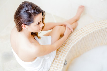 woman in bath: Pretty lady in the bathroom in white towel preparing for a hot bath. Stock Photo
