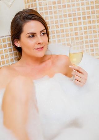 femme brune sexy: Femme magnifique appréciant son champagne dans le bain de mousse.