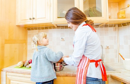 motherly: Mother and daughter cooking food together at home.