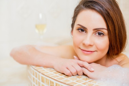 Portrait of a pretty lady smiling in the foam bath at home.
