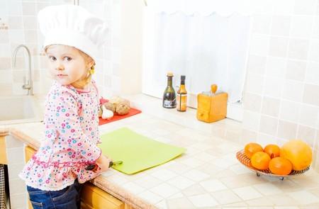 cabeza femenina: Pequeño cocinero lindo ayudar en la cocina.