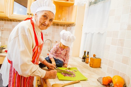 Elderly woman cooking with little girl at home.