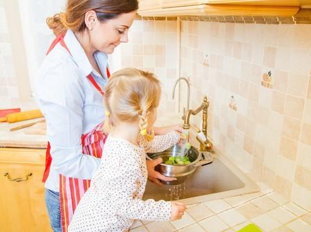 comidas saludables: Hermosa madre con la pequeña hija linda de preparar la comida en la cocina.