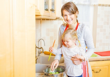 head home: Beautiful mother with cute little daughter preparing food in the kitchen.