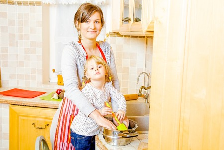 motherly: Helping hand given in the kitchen by little daughter.