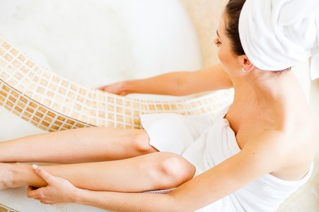 sensible: Pretty lady in the bathroom in white towel preparing for a hot bath. Stock Photo